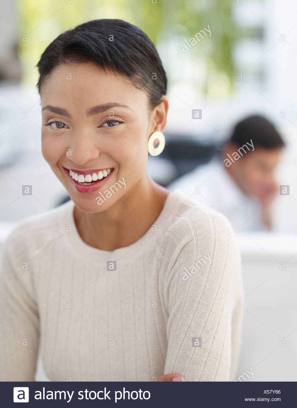 Businesswoman in office looking at camera with businessman in background - Stock Image