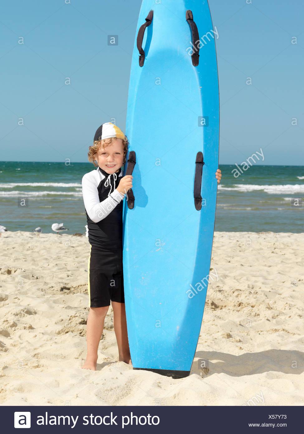 Portrait of cute boy nipper (child surf life savers) next to surfboard at beach, Altona, Melbourne, Australia - Stock Image