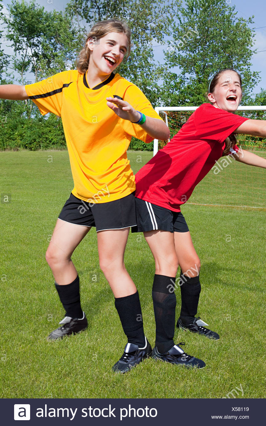 Girl soccer players messing around - Stock Image