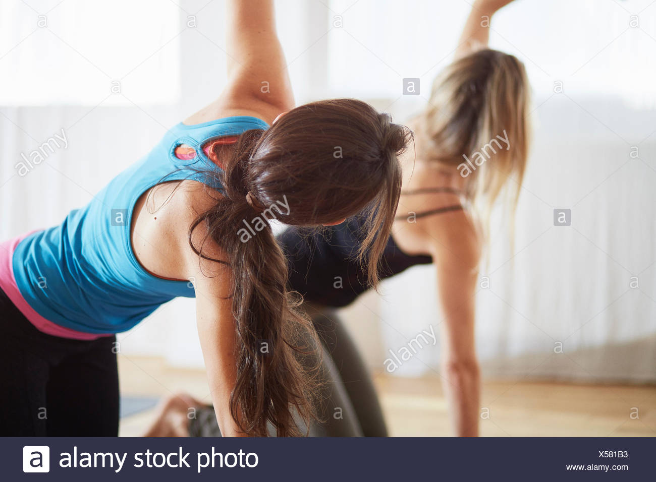Two women kneeling and raising arms in pilates class - Stock Image