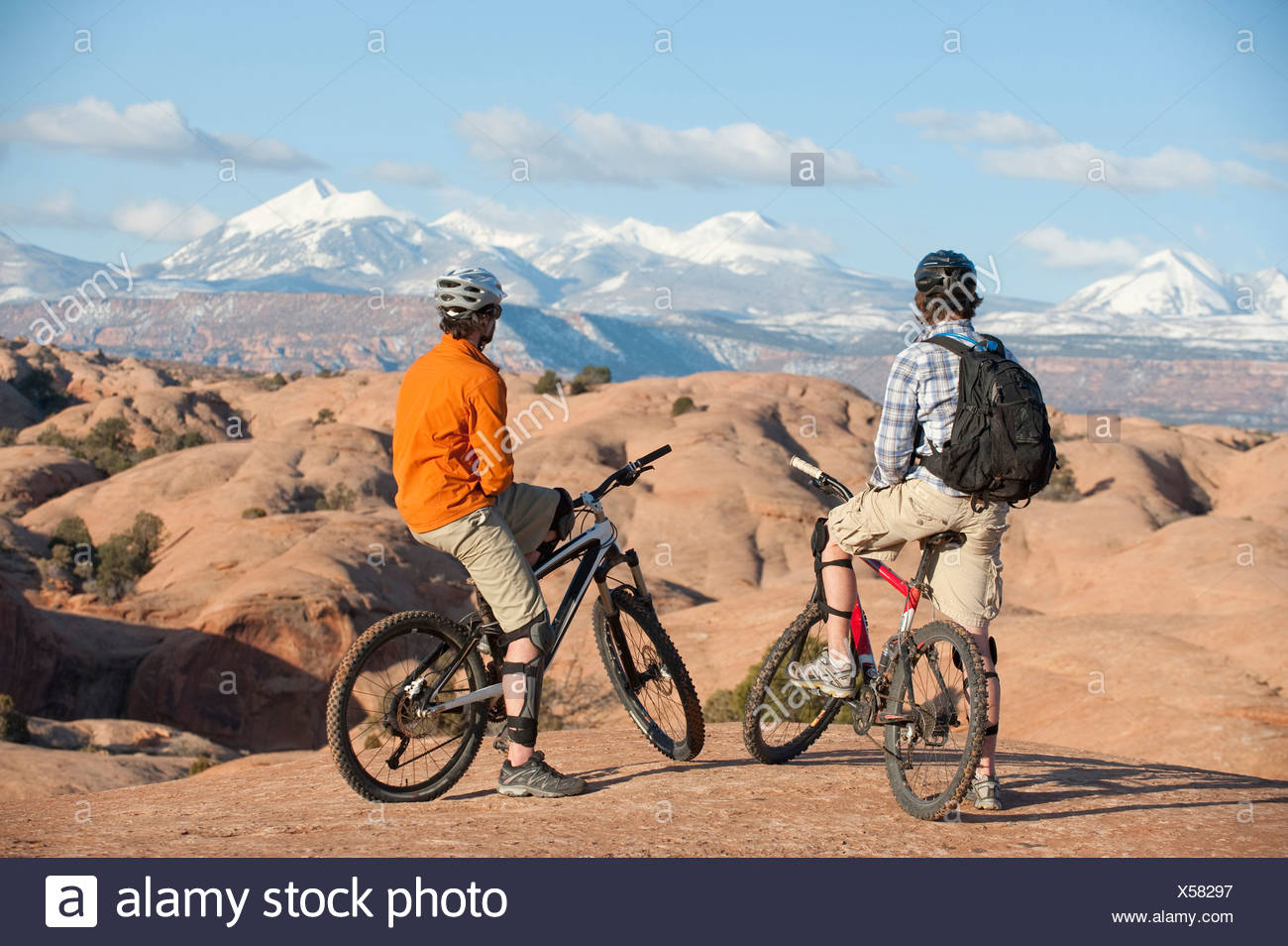 Two young men enjoy the view during a mountain bike trip on the Slickrock Trail, Moab, UT. - Stock Image