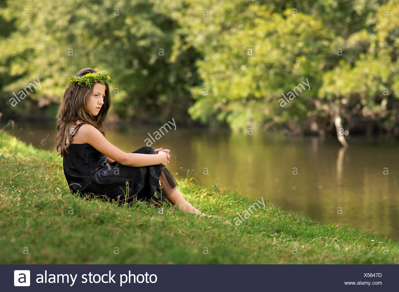 Cute little girl (10-11) with wreath relaxing at river edge - Stock Image
