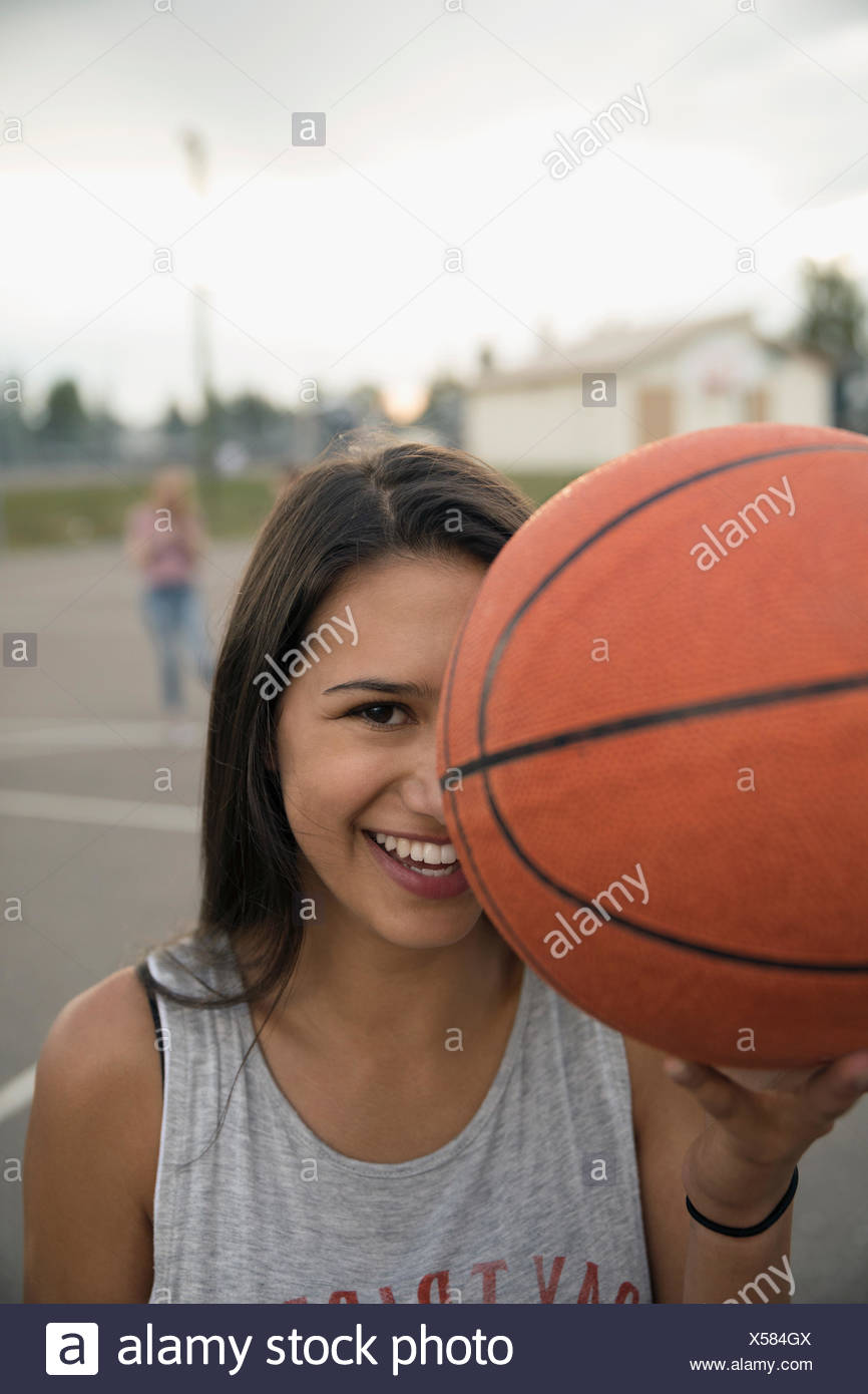 Portrait confident, smiling teenage girl holding basketball on outdoor basketball court - Stock Image