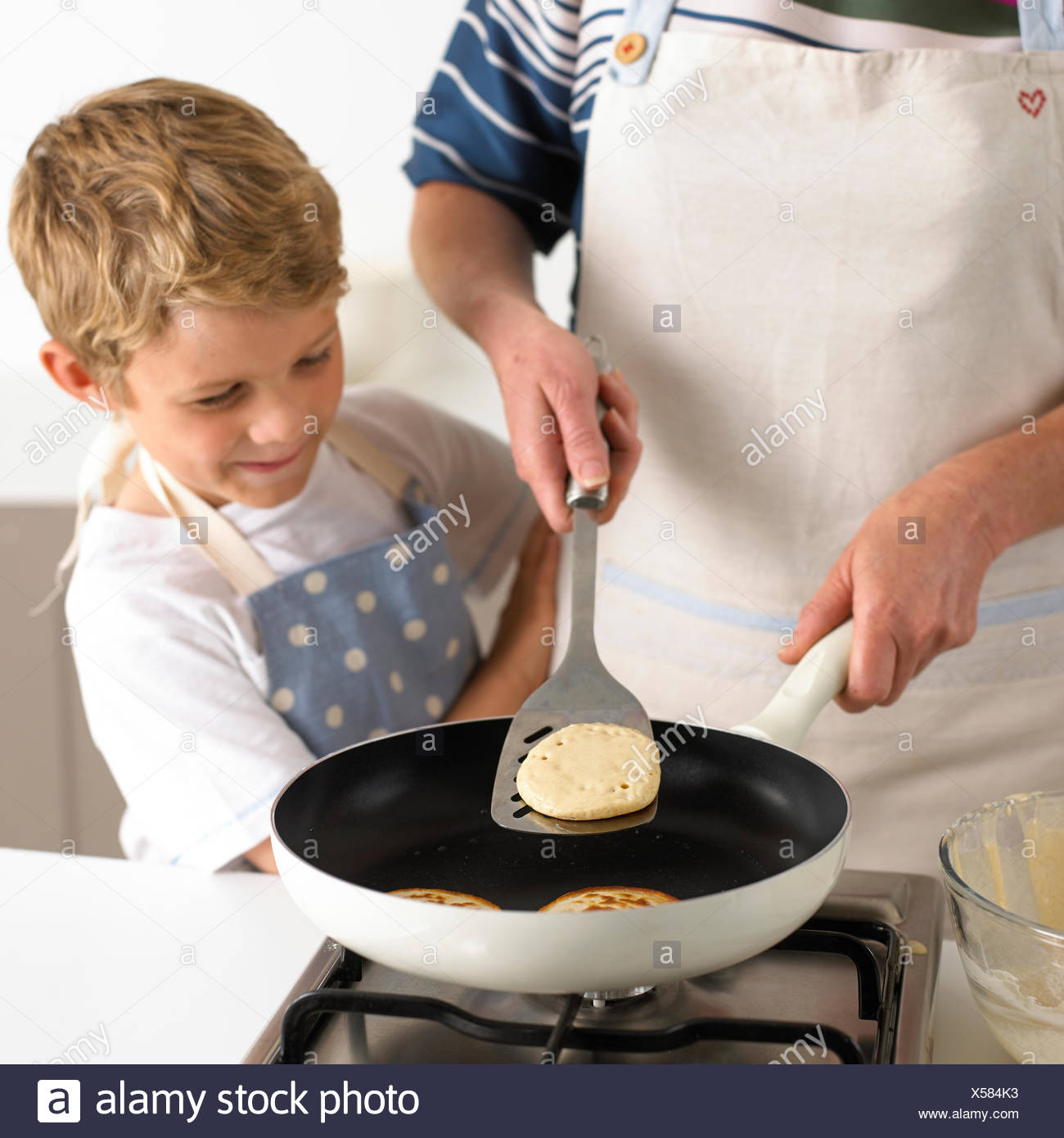 Flipping pancakes in a frying pan - Stock Image