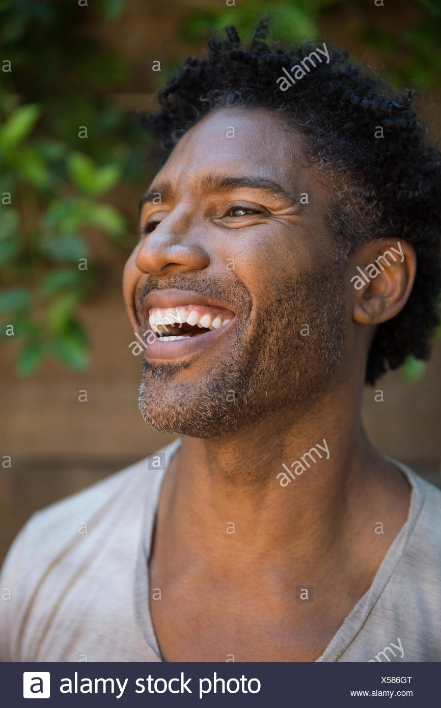 Close up portrait laughing man stubble curly hair - Stock Image