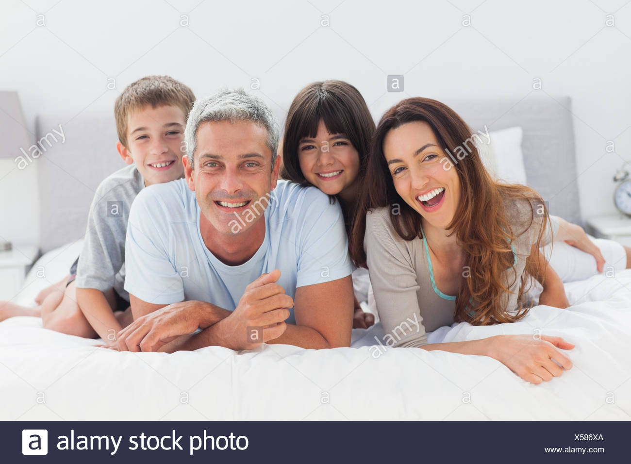 Happy family lying together - Stock Image