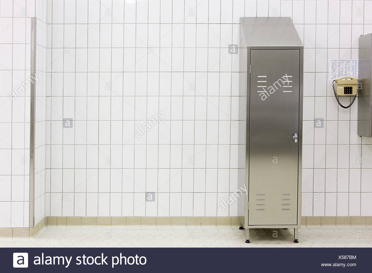 Metal locker in a tiled room - Stock Image