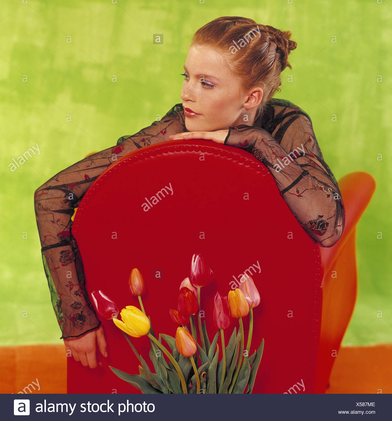 Armchairs, girls, red-haired, view side view, tulips woman, young, 15 - 20 years, hairstyle, make-up, top blouse, beauty, youth, Beauty, course, naturalness, upholstered chair, back, lean, rest on, chair back, back rest, side glance, flowers, inside - Stock Image