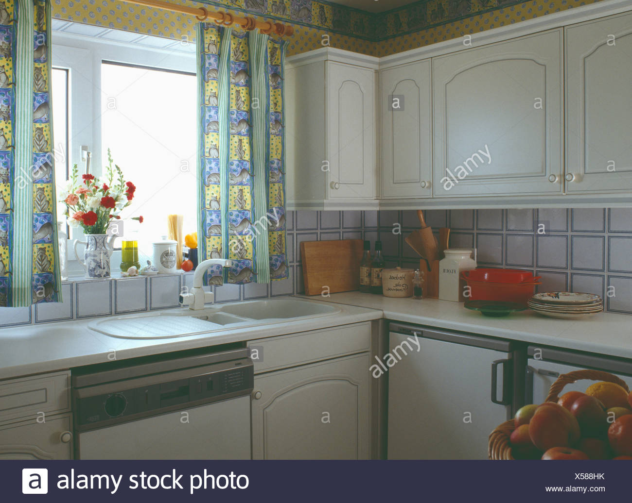 Yellow Patterned Curtains Above White Sink In Small Nineties Kitchen Stock Photo Alamy