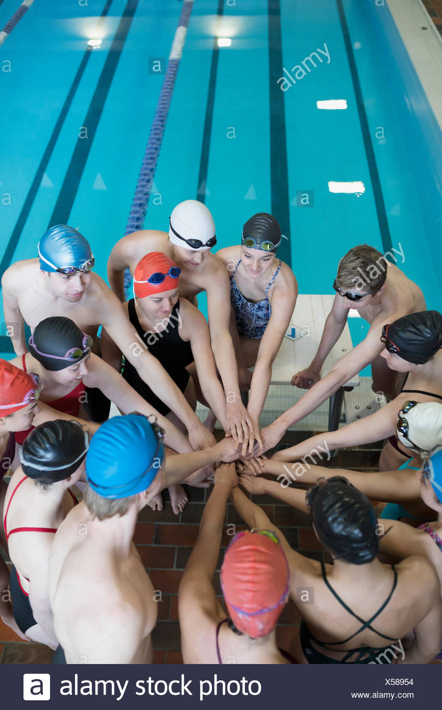 Swimming team connecting hands in huddle at swimming pool - Stock Image