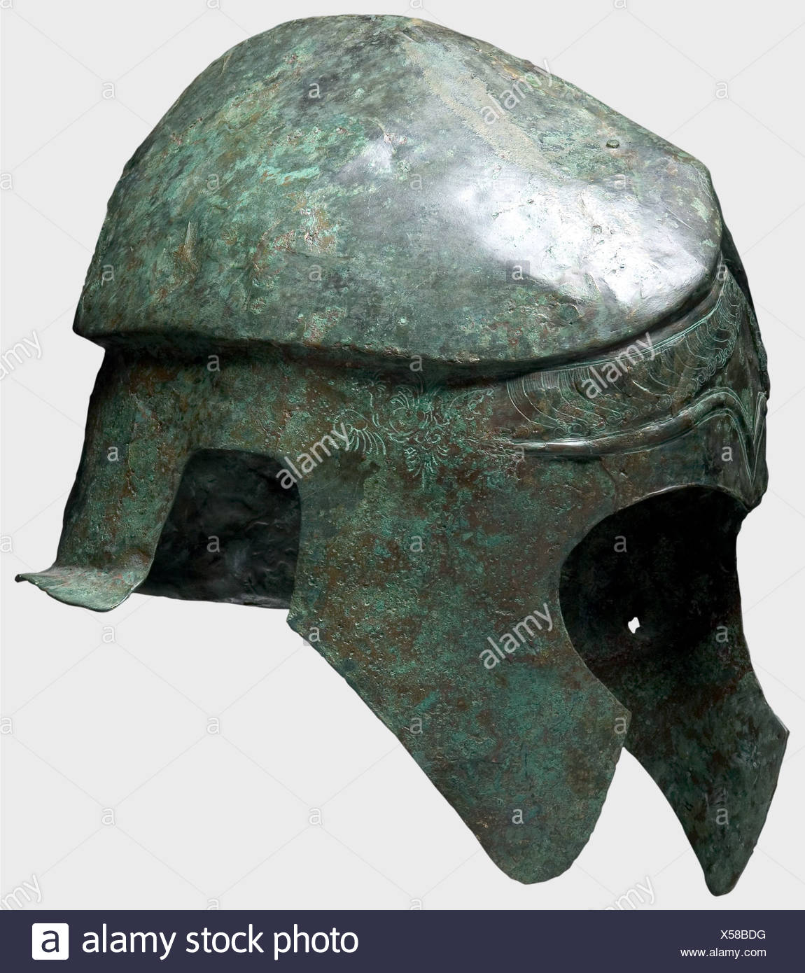 A Chalcidian helmet, 5th/4th century B.C. Bronze. Narrow elongated skull with a carinated and crested crown, holes for the plume attachment, large cheek pieces and ear cutouts, and a short flaring neck guard. The forehead has decorative eyebrows in relief and richly chiselled decorative palmettos, serpents' heads, locks of hair, and floral ornamentation. The right cheek piece has a nail hole, presumably from the votive offering of the helmet in a sanctuary. Height 23 cm. Weight 828 g. The metal is distorted, but well-preserved with dark-green patina. The interi, Additional-Rights-Clearences-NA - Stock Image
