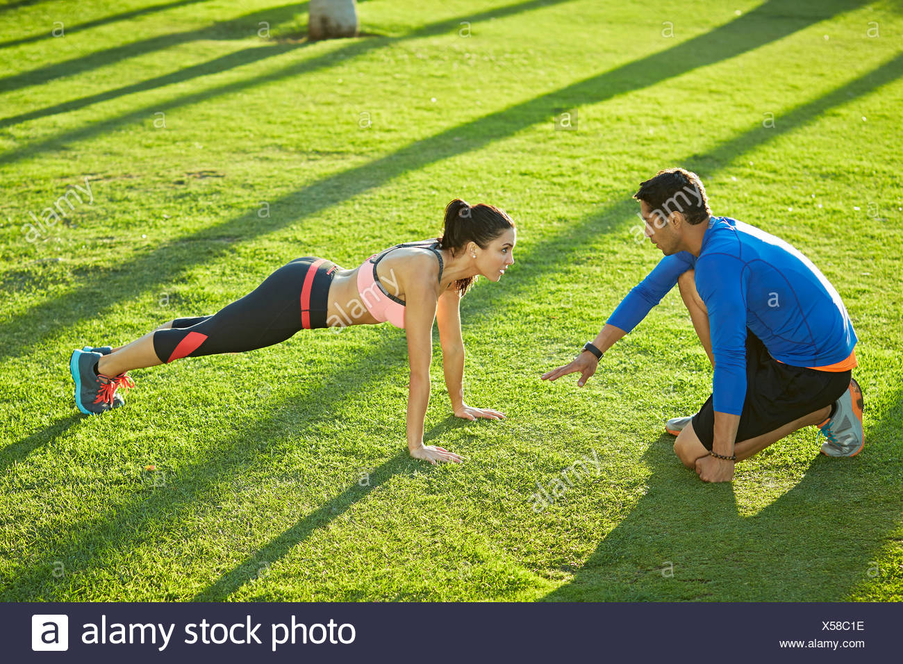 Personal trainer with woman doing plank exercise Stock Photo