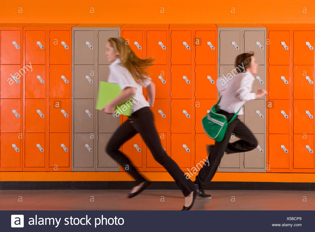 Students rushing past school lockers - Stock Image
