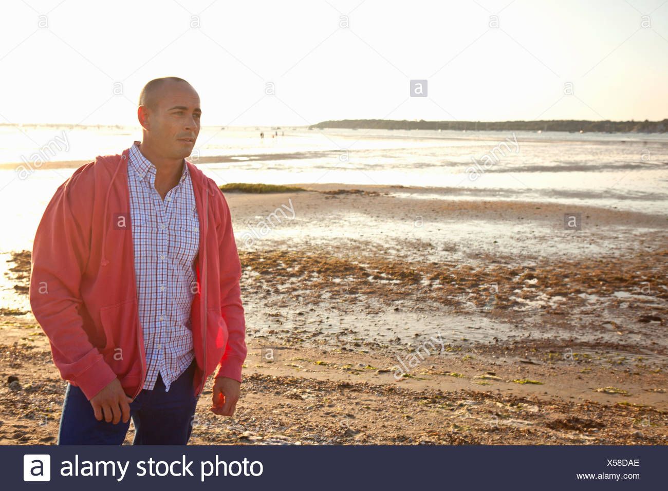 Man looking into distance on beach - Stock Image