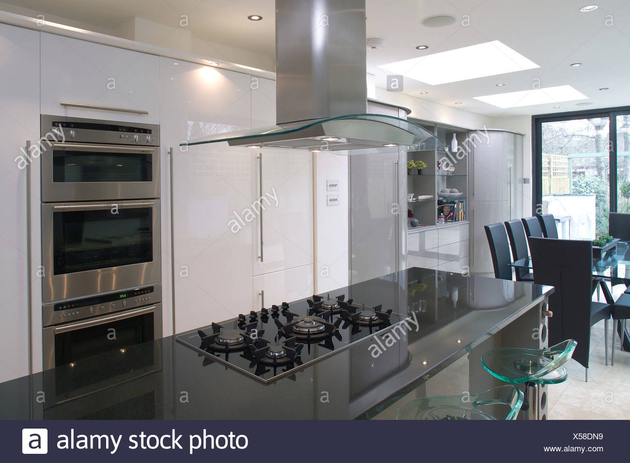 Extractor Fan Above Hob In Black Granite Island Unit In Modern Openplan Kitchen With Wall Mounted Oven Stock Photo Alamy