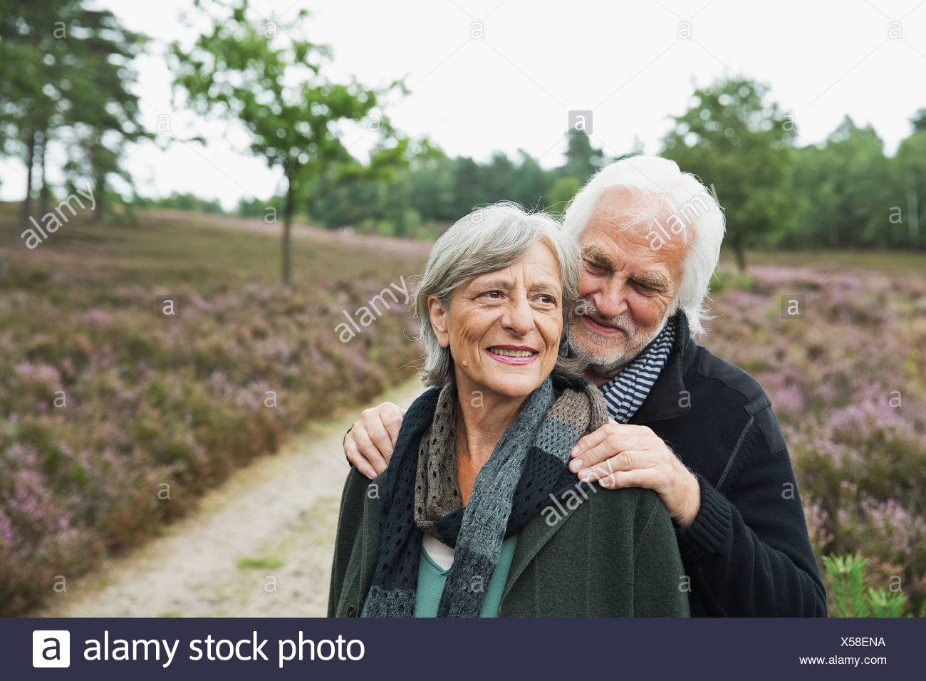 Senior couple, man with hands on woman's shoulders - Stock Image
