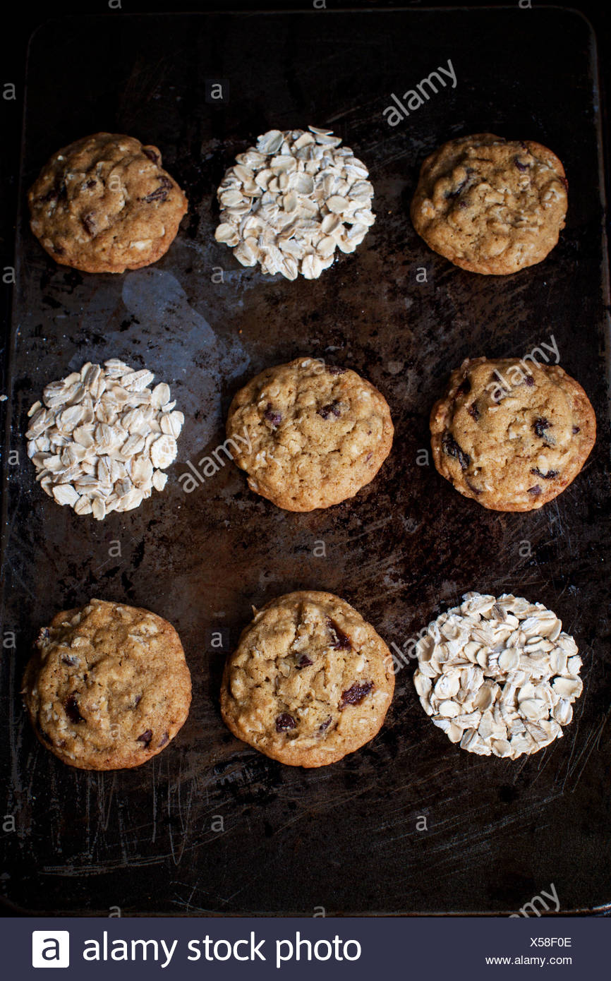 Rich oat cookies with raisin and chocolate chips, having crunchy edges and flavorful chewy center. Set up onto a vintage backgro - Stock Image