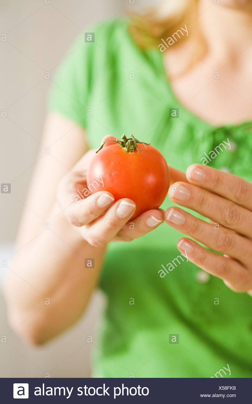 Woman with a tomato, Sweden. - Stock Image