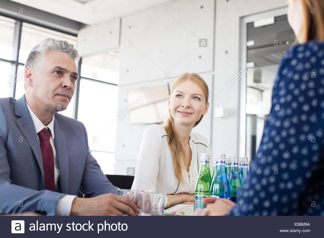 Smiling young businesswoman with colleagues in board room - Stock Image