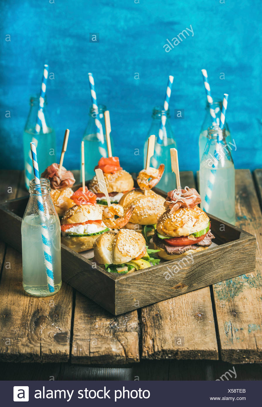 Home party food concept. Different burgers with sticks in wooden tray and lemonade in bottles with straws on rustic shabby table, bright blue painted - Stock Image