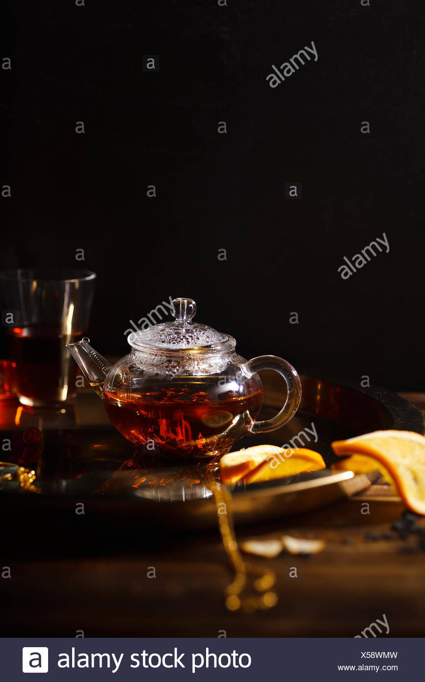 Small glass teapot and glasses with hot black tea, dried rose petals, pocket magnifier on golden chain, squeezed orange slice on golden tray. Evening  - Stock Image