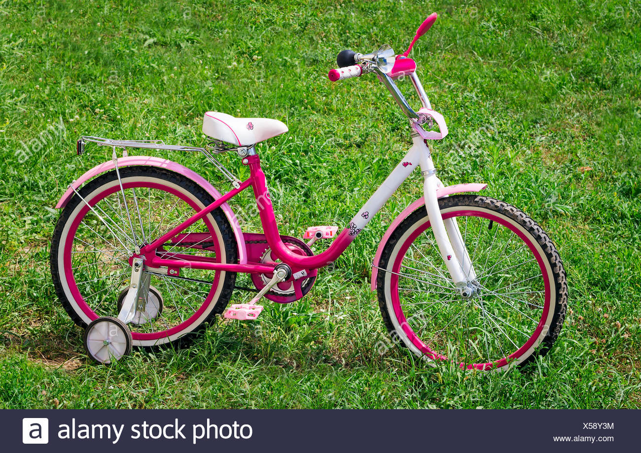 The bicycle for the girl on a green lawn. - Stock Image