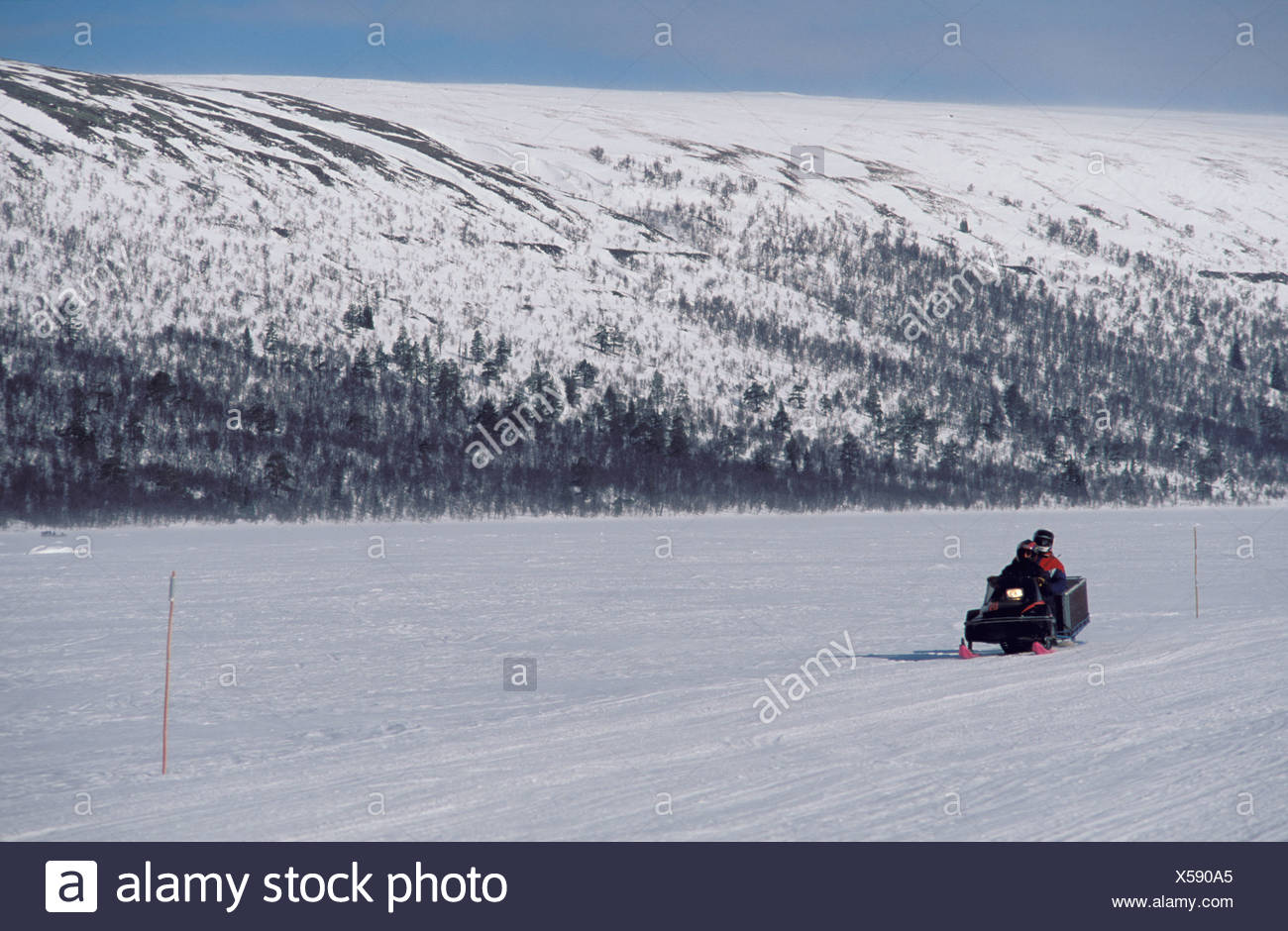 Snowmobile driving across snowy landscape Norway - Stock Image
