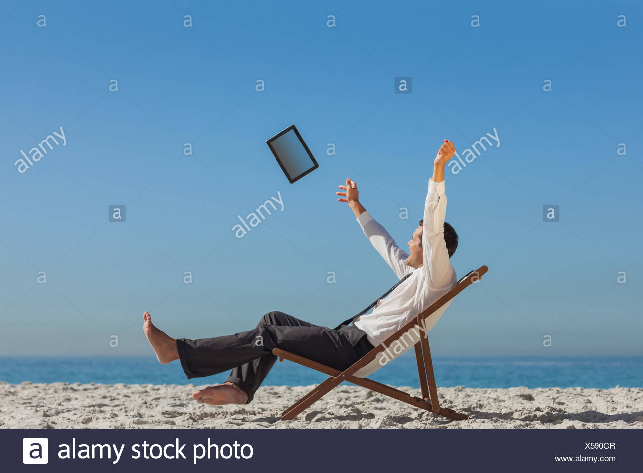 76b4ad31fa Victorious young businessman relaxing on his deck chair throwing his ...