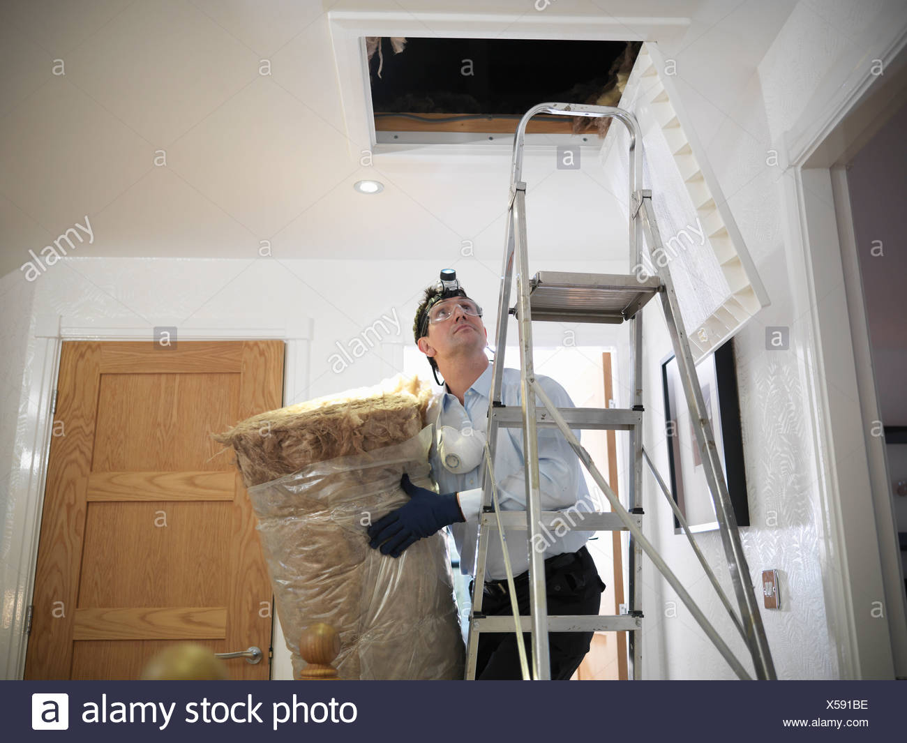 Worker carrying insulation to attic - Stock Image