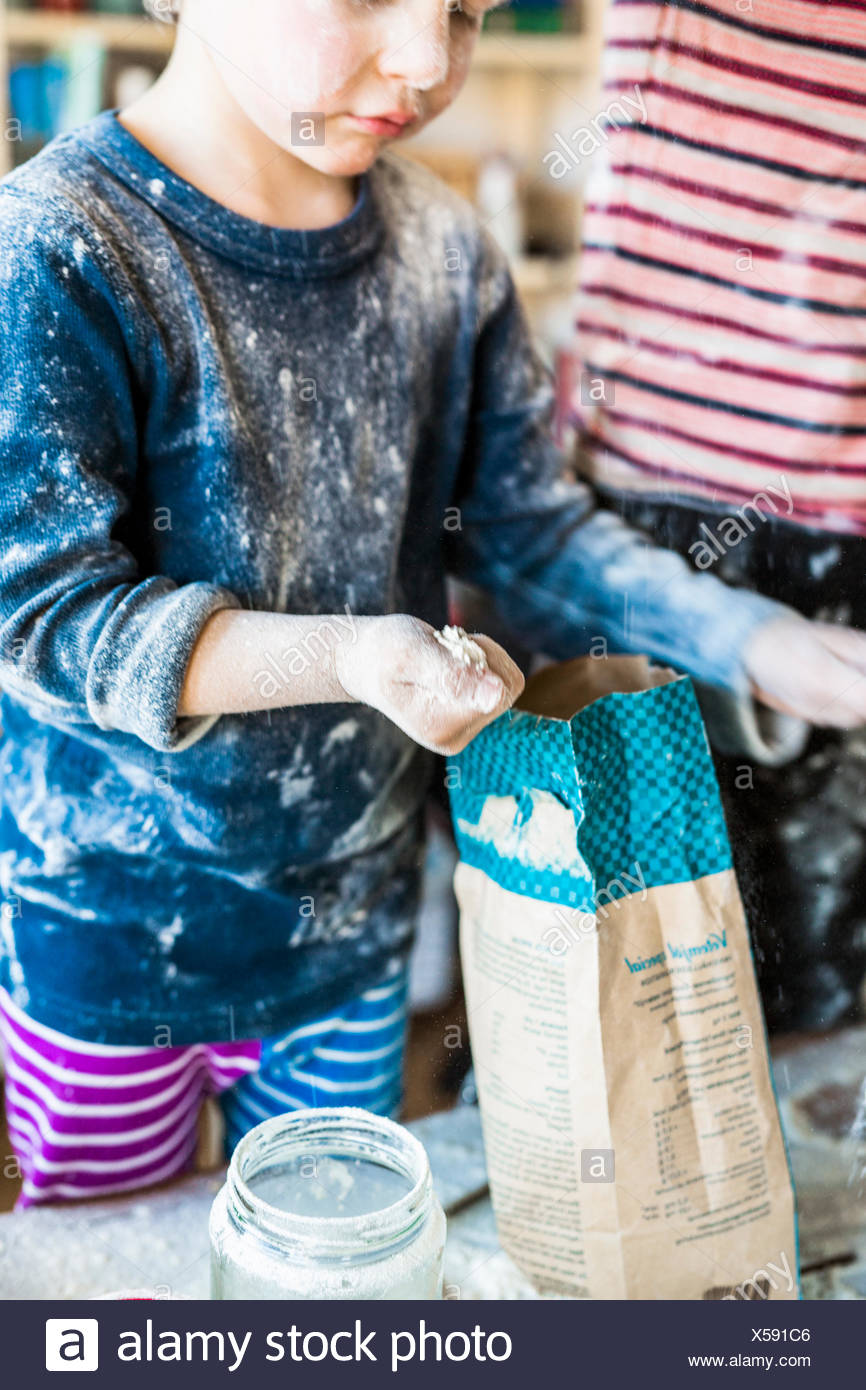 Messy boy holding flour while baking at home - Stock Image