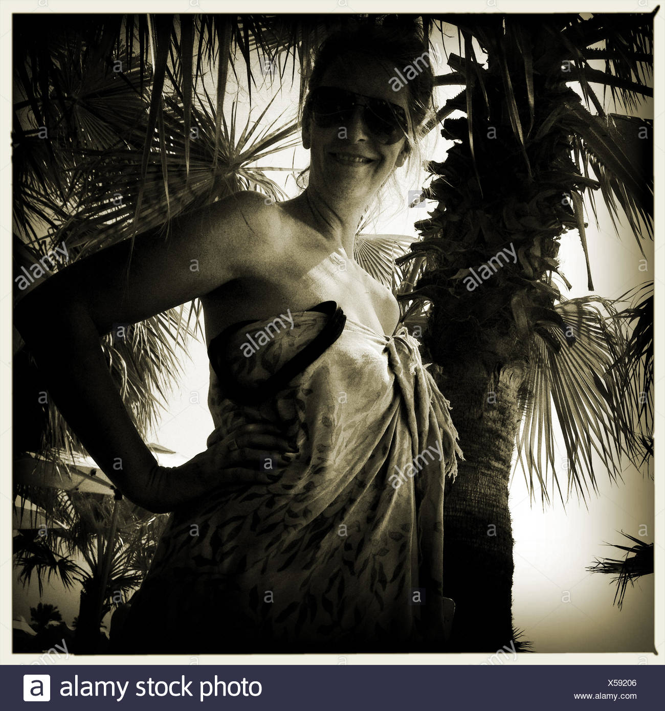 Portrait of woman under palm tree - Stock Image