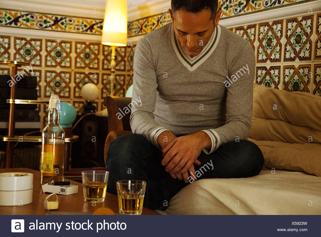 Depressed man sitting with alcohol on table - Stock Image