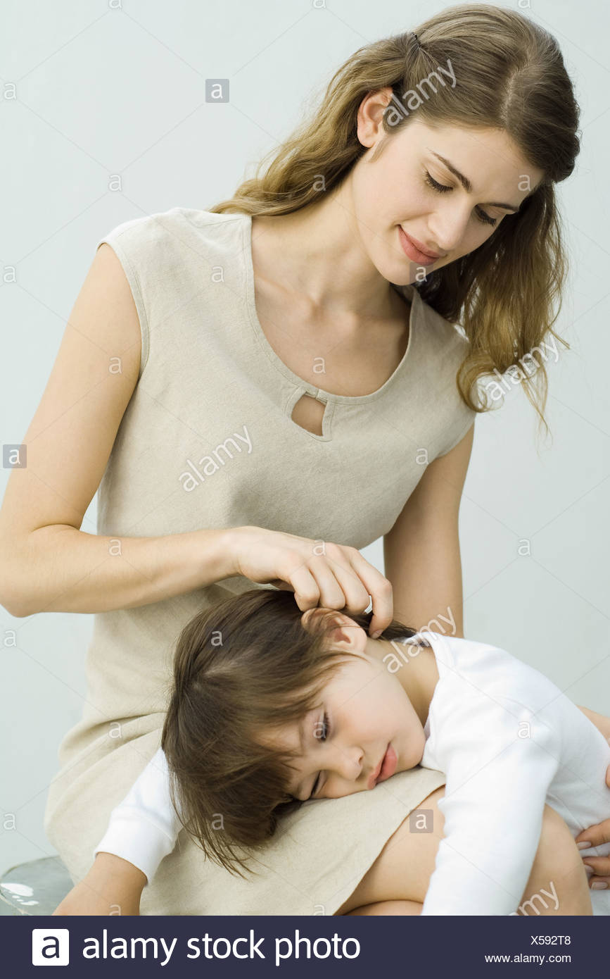 Little boy lying in mother's lap, woman stroking son's hair - Stock Image