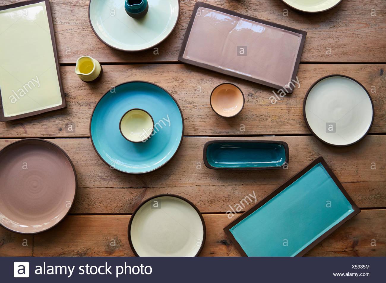 Handmade earthenware on a wooden table, overhead shot - Stock Image