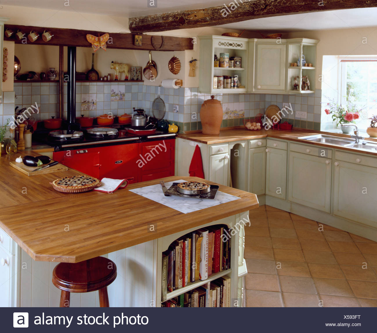 Island Unit With Wooden Worktop In Traditional Country Kitchen With Red Aga  Double Oven And Terracotta Floor Tiles