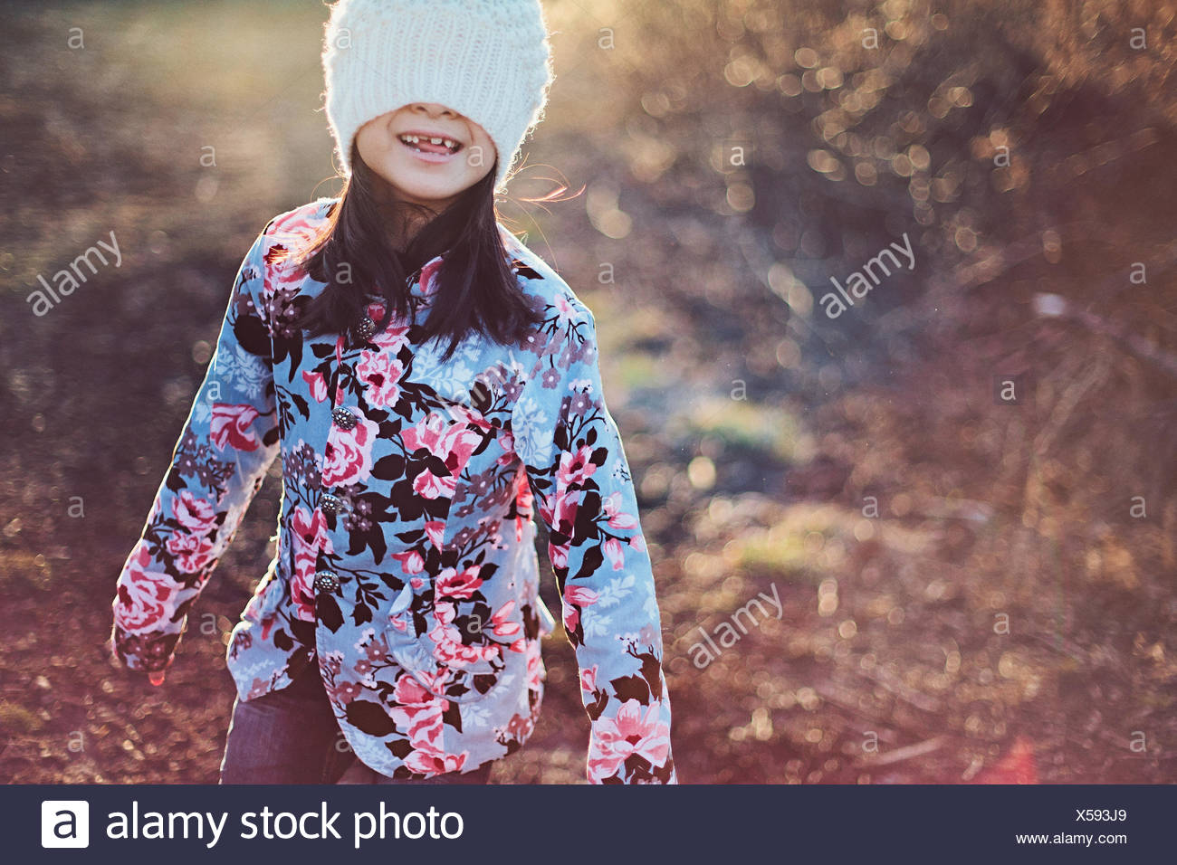 Girl (8-9) covering face with white winter hat - Stock Image