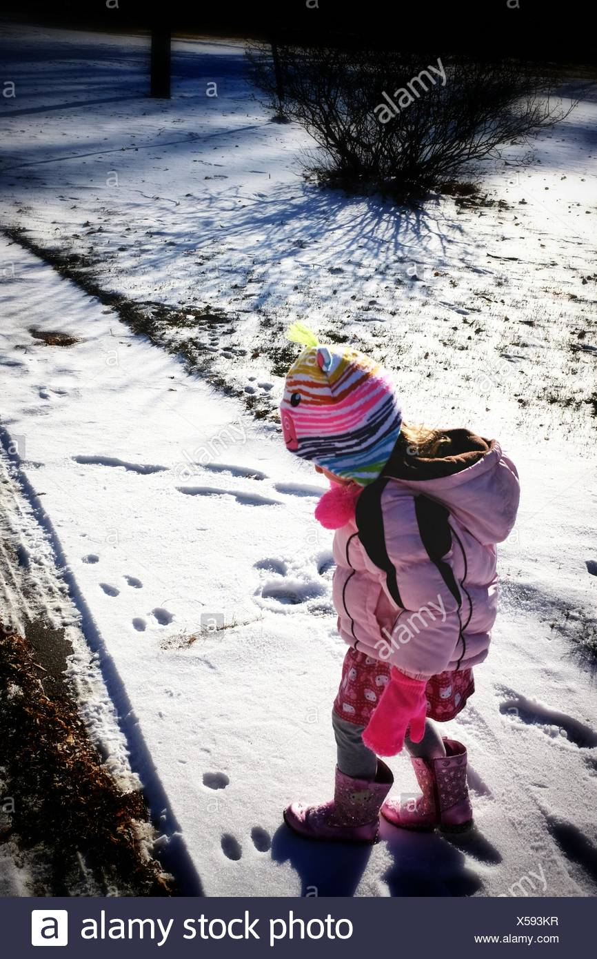 Cute Girl Walking On Snow Covered Landscape During Winter - Stock Image