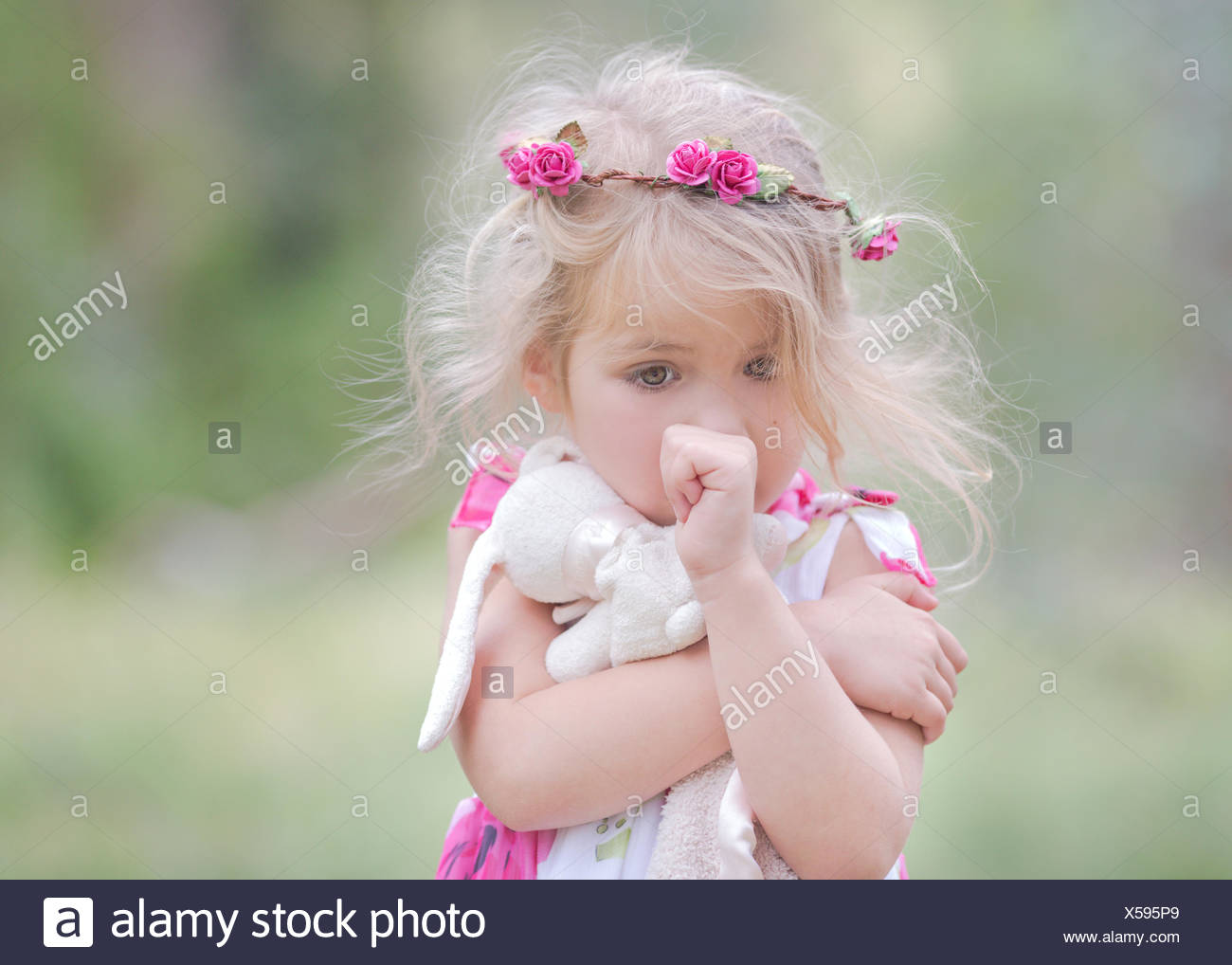 Portrait of a girl sucking her thumb and clutching her soft rabbit toy, California, USA Stock Photo