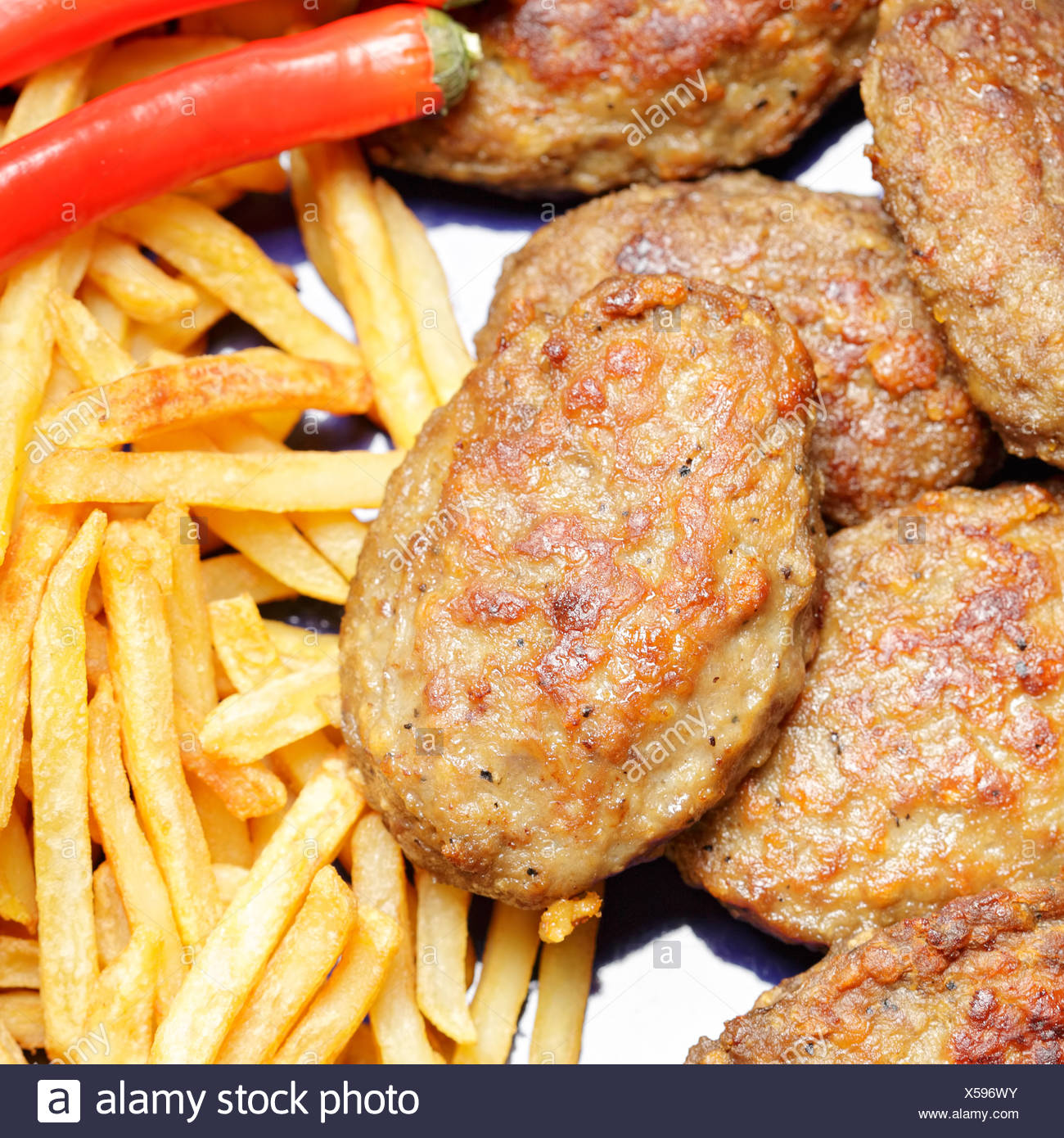 Cutlets with french fries and chili - Stock Image