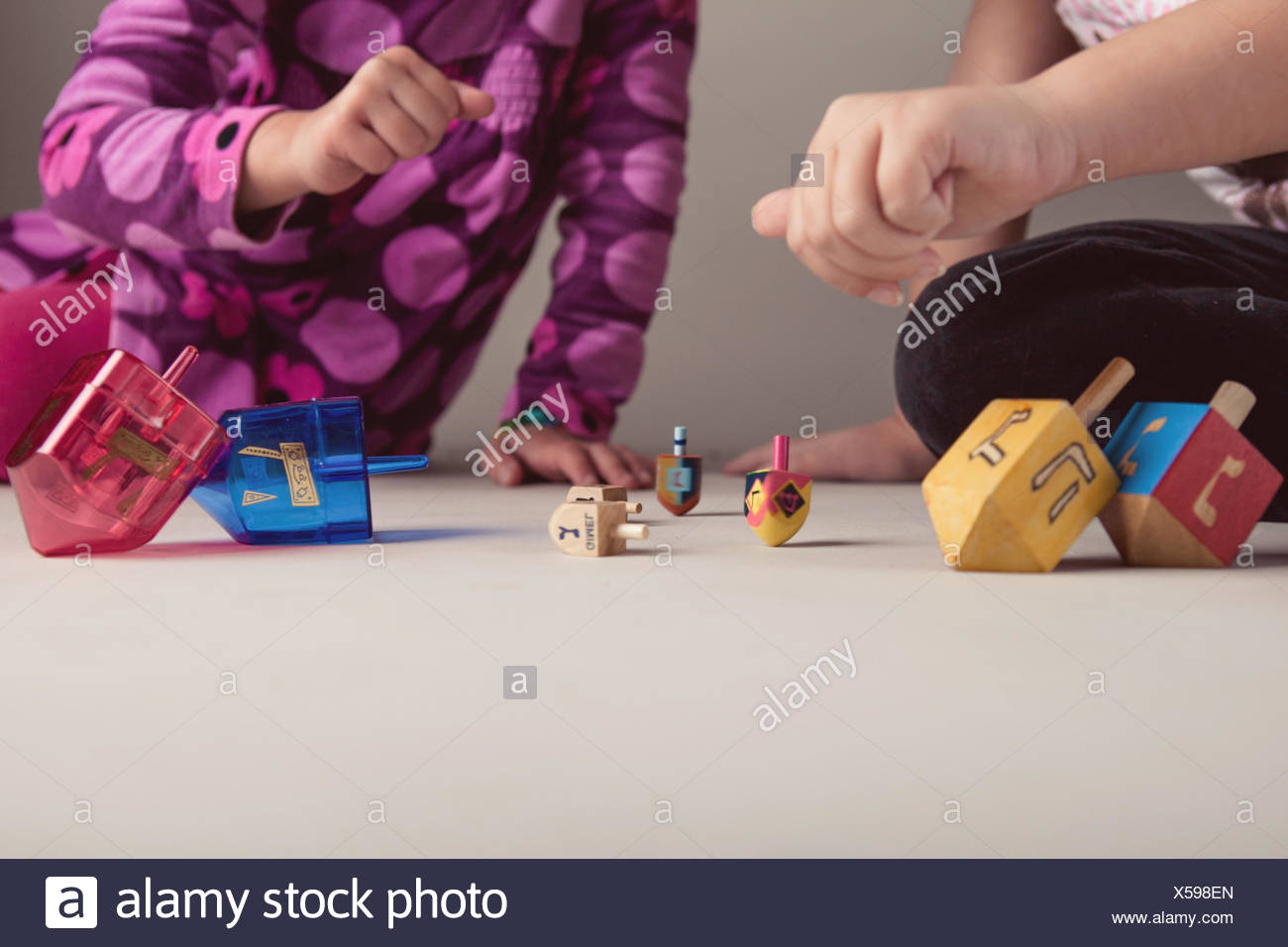 Two girls playing with dreidels to celebrate Hanukkah - Stock Image