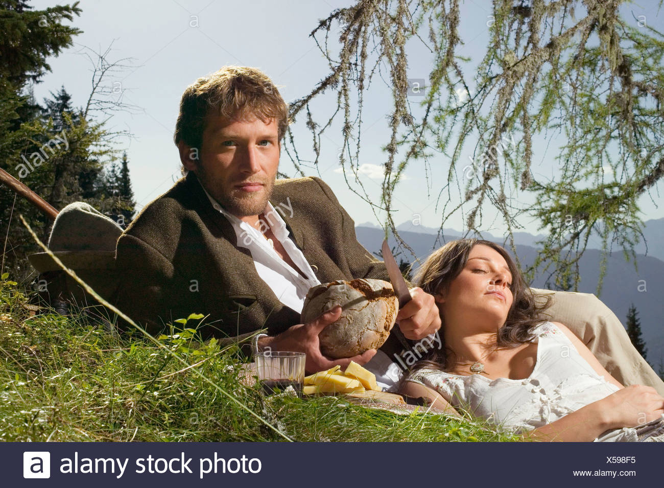Young couple lying in meadow, having picnic - Stock Image