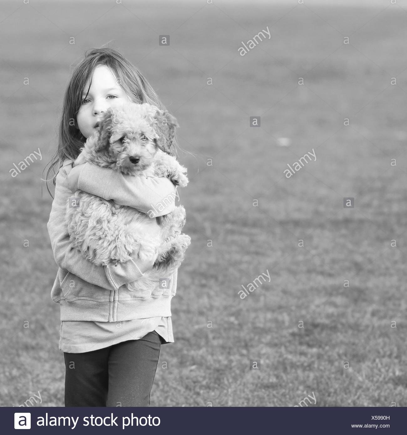 Girl carrying puppy dog - Stock Image