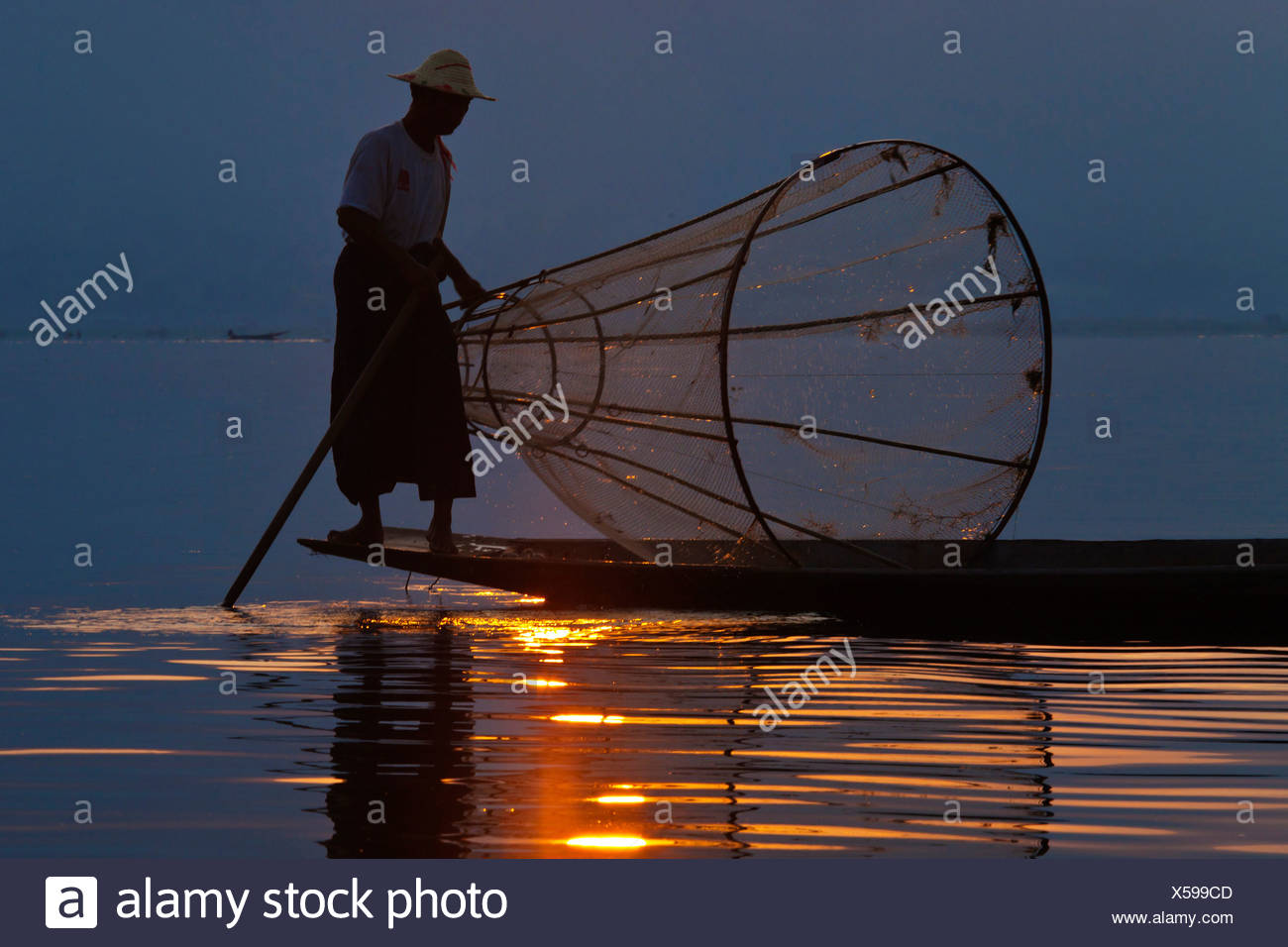fisher man at dawn is still done in the traditonal way with small wooden boats, fishing nets and leg rowing, Inle lake, Burma, Inle See - Stock Image