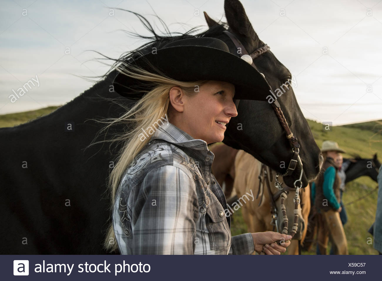 Female rancher with horse looking away - Stock Image