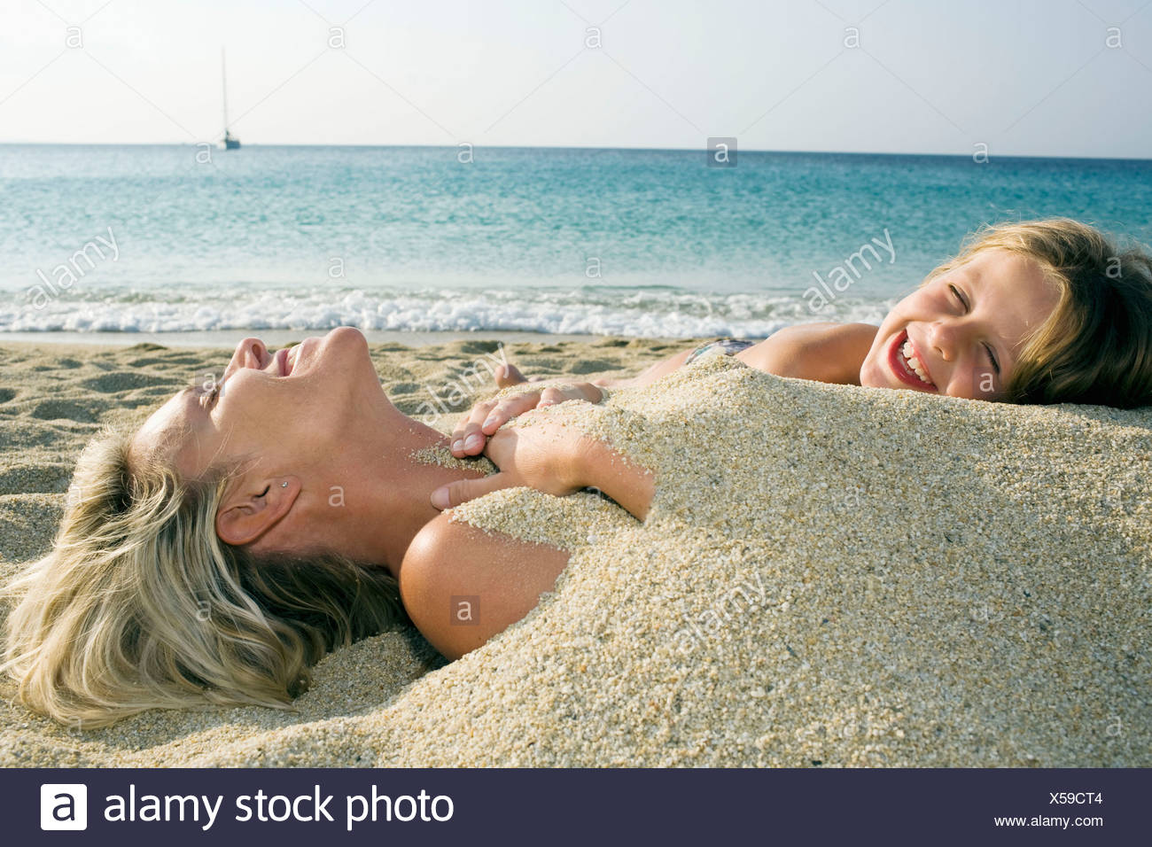 Woman buried in sand at the beach with young girl leaning on her and laughing. Stock Photo