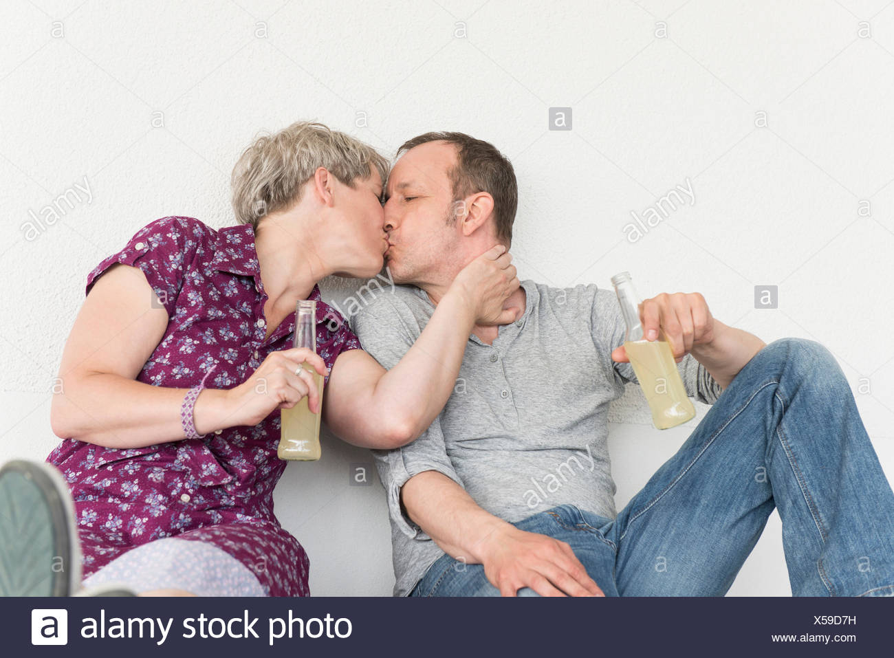 mature couple kissing each other with drink bottle stock photo