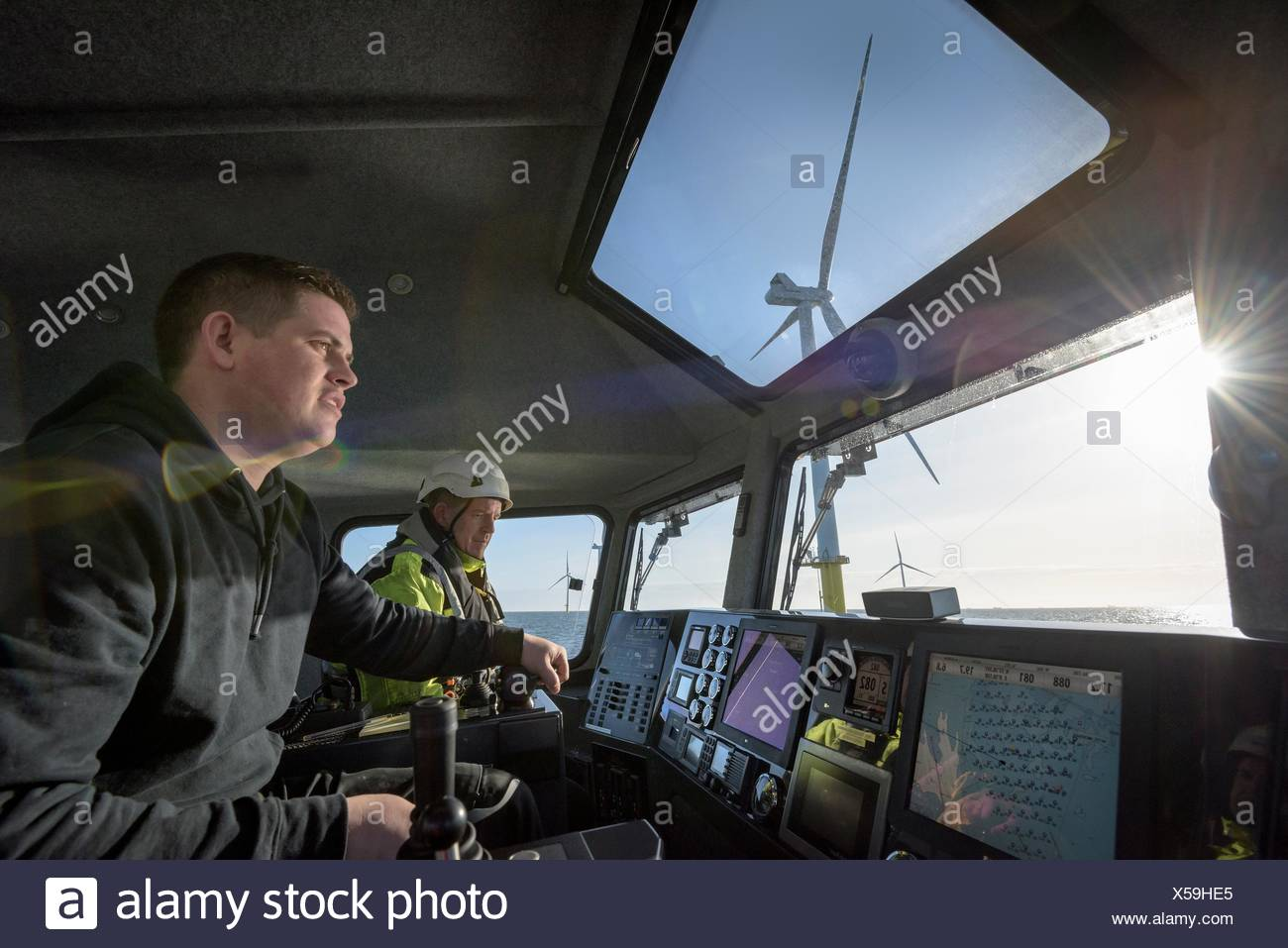 Captain and mate steer boat through offshore wind farm - Stock Image