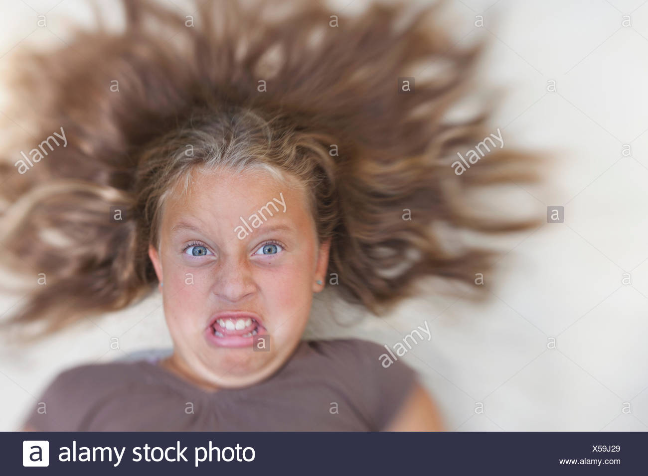 USA, Maryland, Howard County, Dayton, Girl (8-9) with tousled blond hair making a face - Stock Image