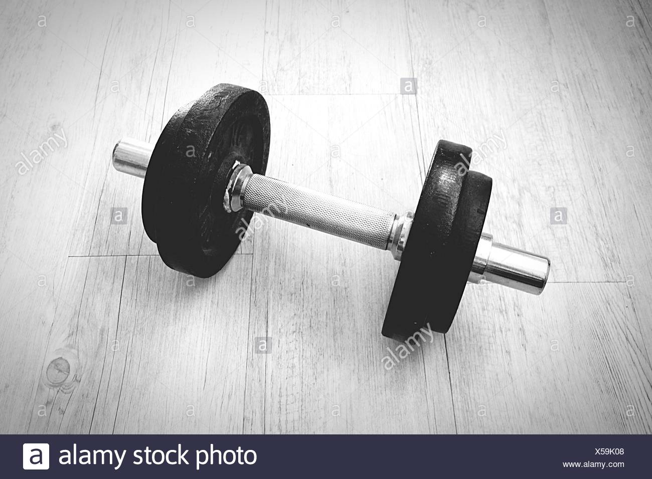 High Angle View Of Dumbbell On Hardwood Floor - Stock Image