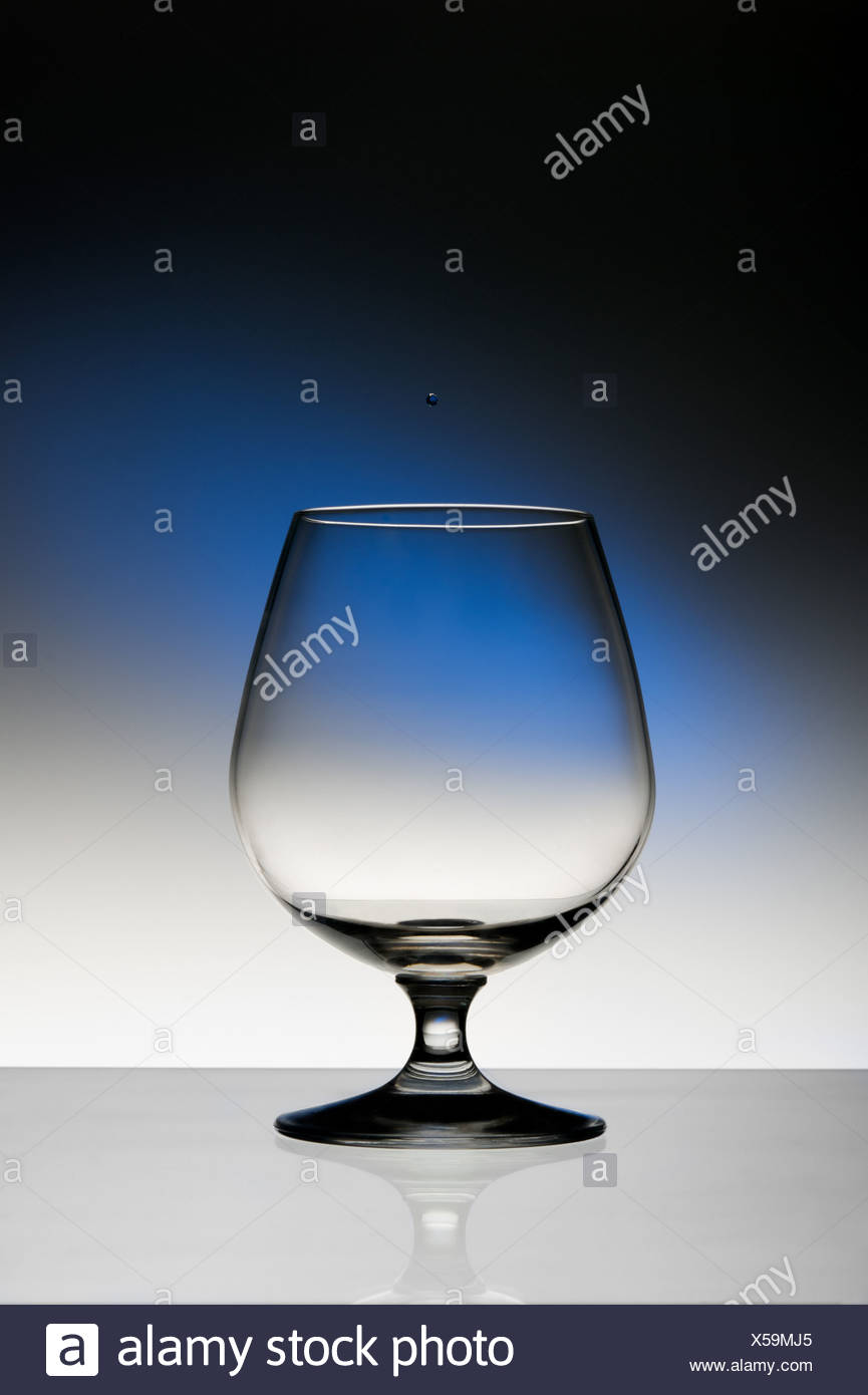 Empty cognac wineglass on dark background with blue spot - Stock Image